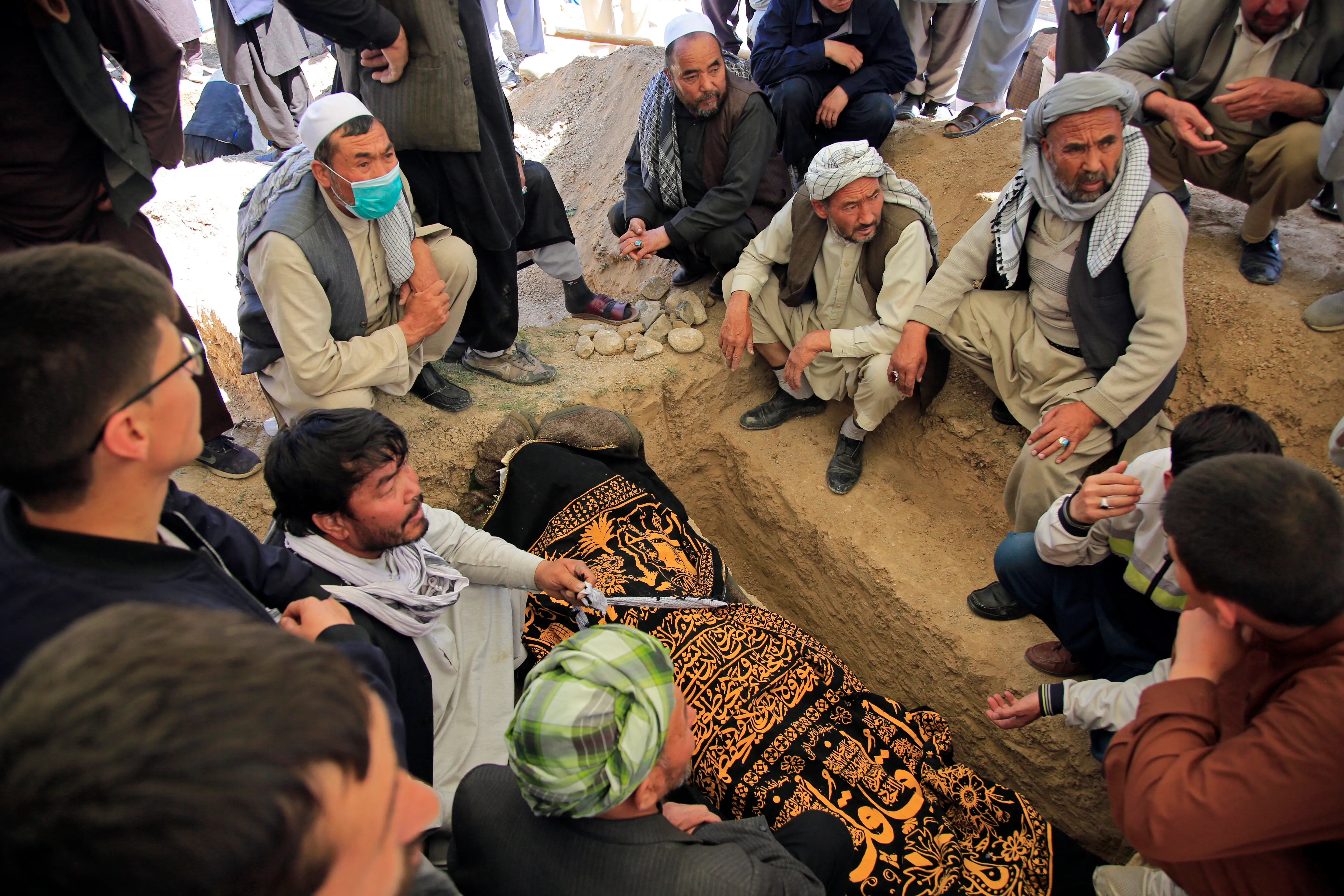 Afghan men bury a victim of deadly attacks on May 8 near a school in a cemetery west of Kabul, Afghanistan on May 9, 2021. The Interior Ministry on Sunday announced the terrible toll bomb attacks at the entrance to a girls' school.  in the Afghan capital has soared to around 50 people, many of whom were students between the ages of 11 and 15, and the number of injured in Saturday's attack also rose to more than 100.