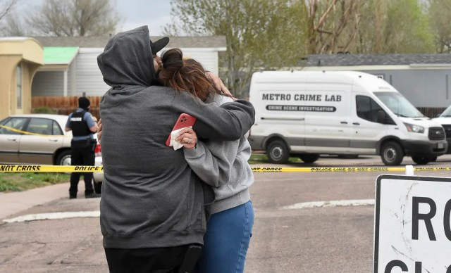 Freddy Marquez kisses the head of his wife, Nubia Marquez, near the scene where her mother and other family members were killed in a mass shooting early Sunday, May 9, 2021, in Colorado Springs, Colo.