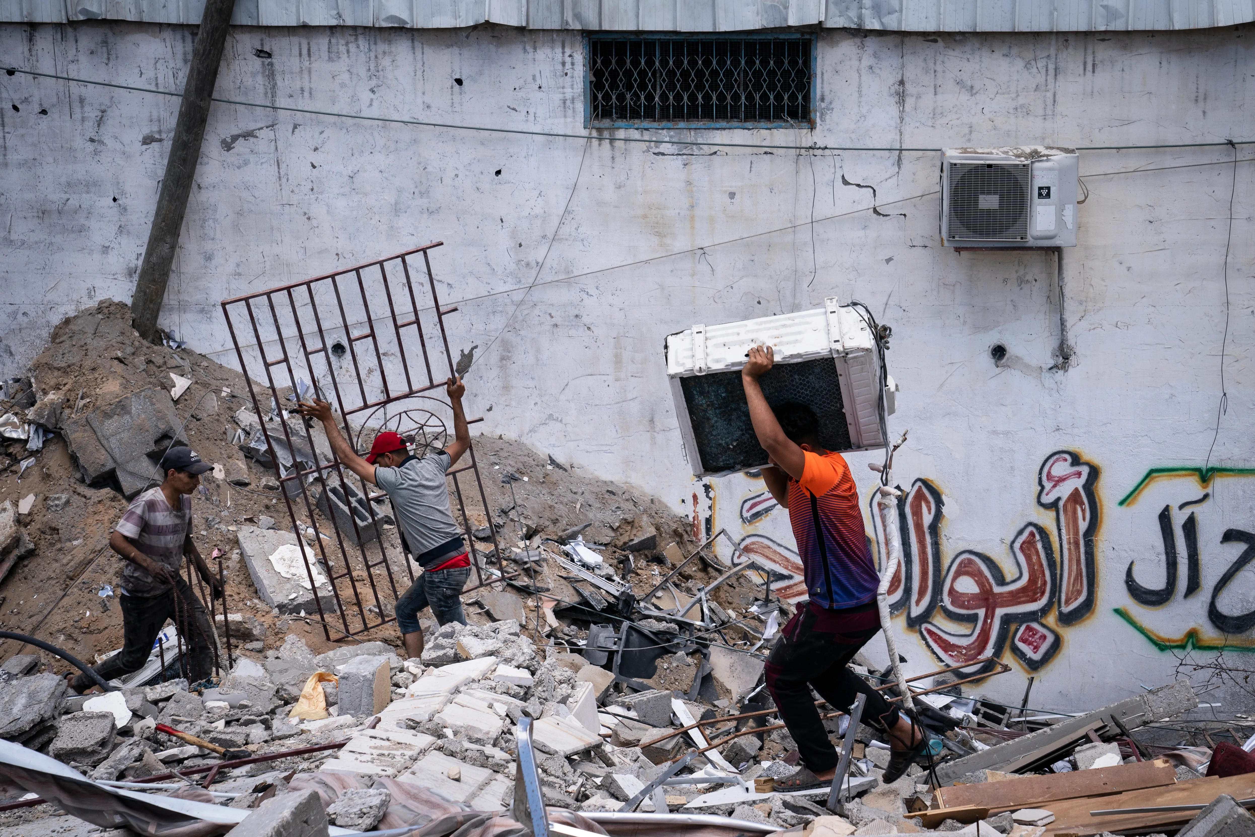 People reclaim valuable materials from a debris pile of a building destroyed by an airstrike prior to a cease-fire reached after an 11-day war between Gaza's Hamas rulers and Israel, in Gaza City, Saturday, May 22, 2021.