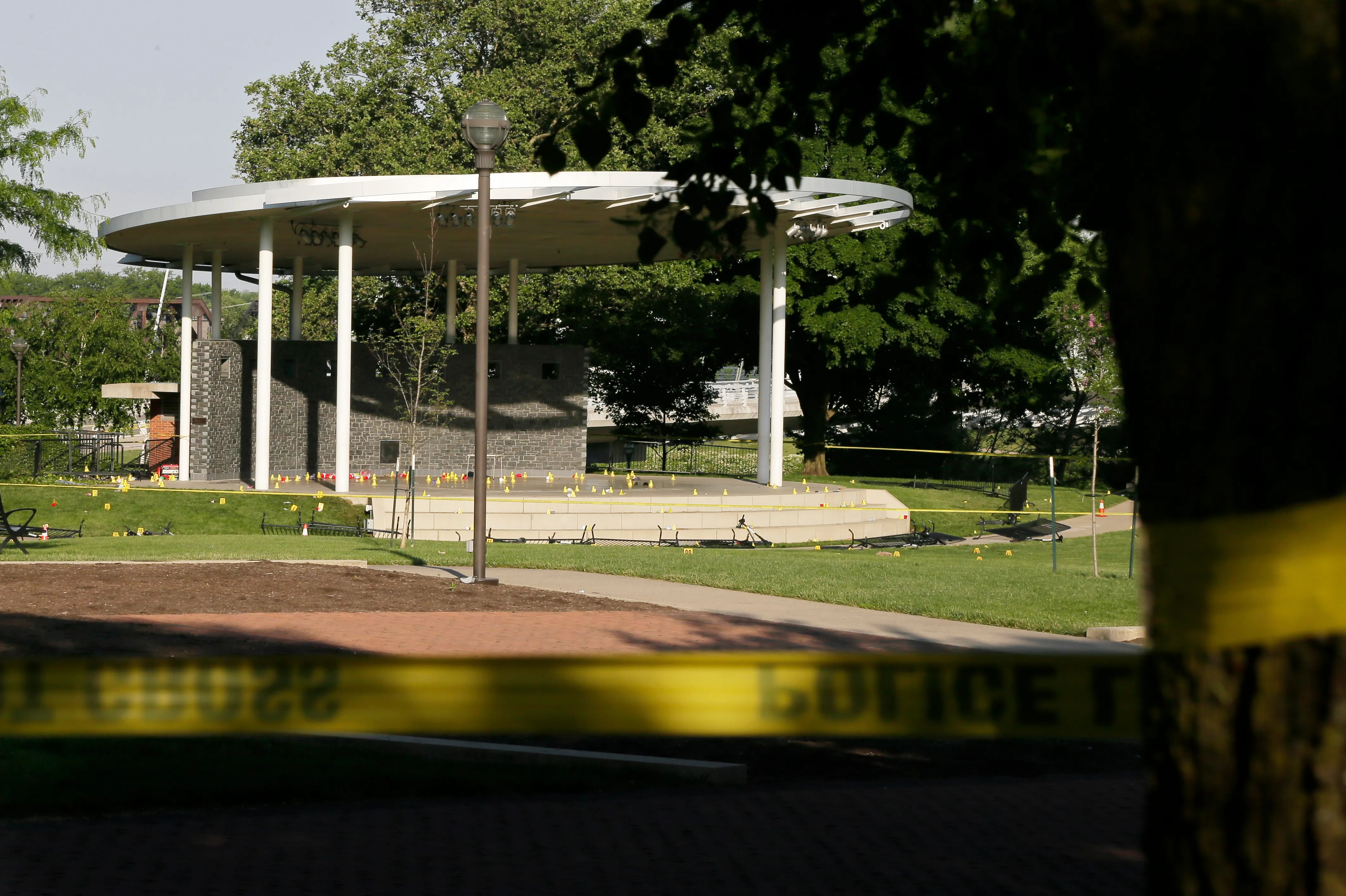 Crime scene tape surrounds Bicentennial Park in downtown Columbus on Sunday morning, May 23, 2021, as Columbus police investigate a shooting late Saturday night that killed one and injured several others. The small yellow cones all over the stage and surrounding grass areas mark bullet casings and other evidence.