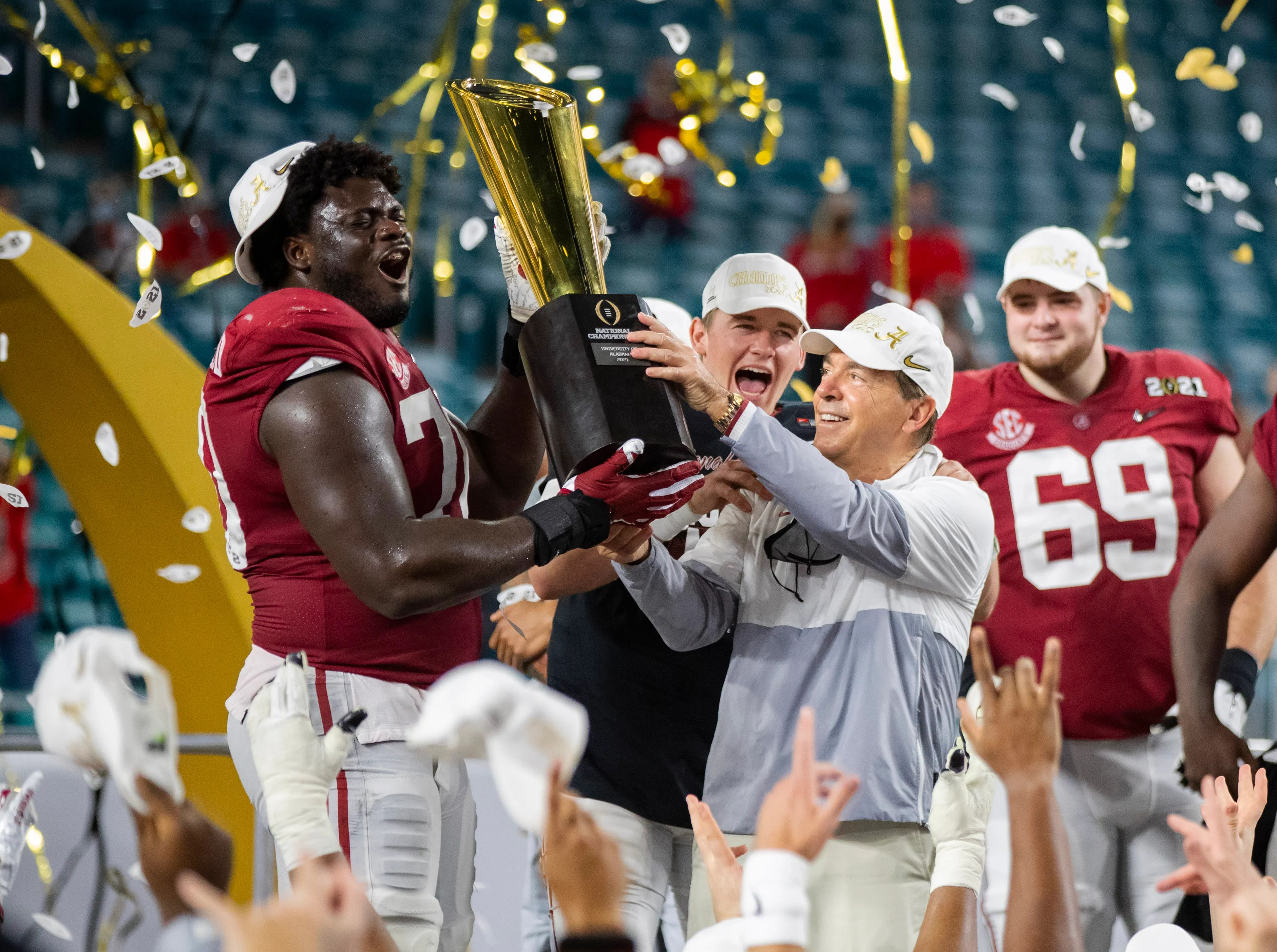 Alabama coach Nick Saban and offensive lineman Alex Leatherwood celebrated with the National Championship trophy after defeating Ohio State in the 2021 CFP National Championship game.