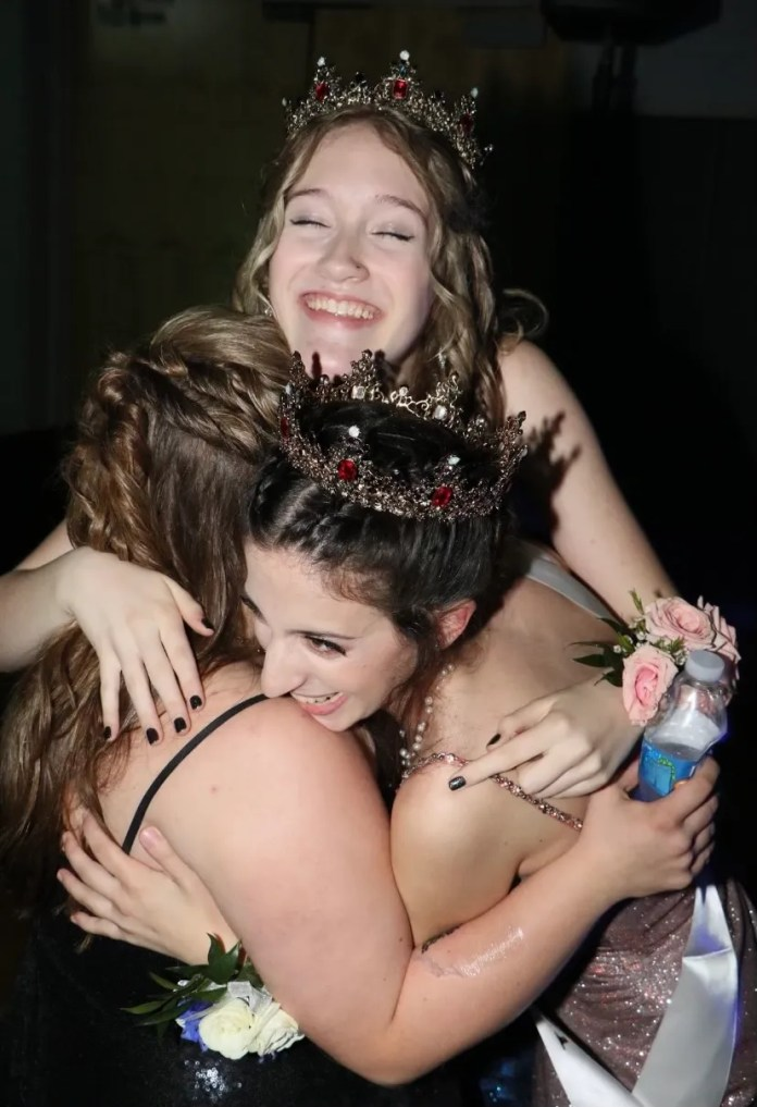 Carly Levy and Courtney Steiner embrace with a friend as they're crowned prom queens