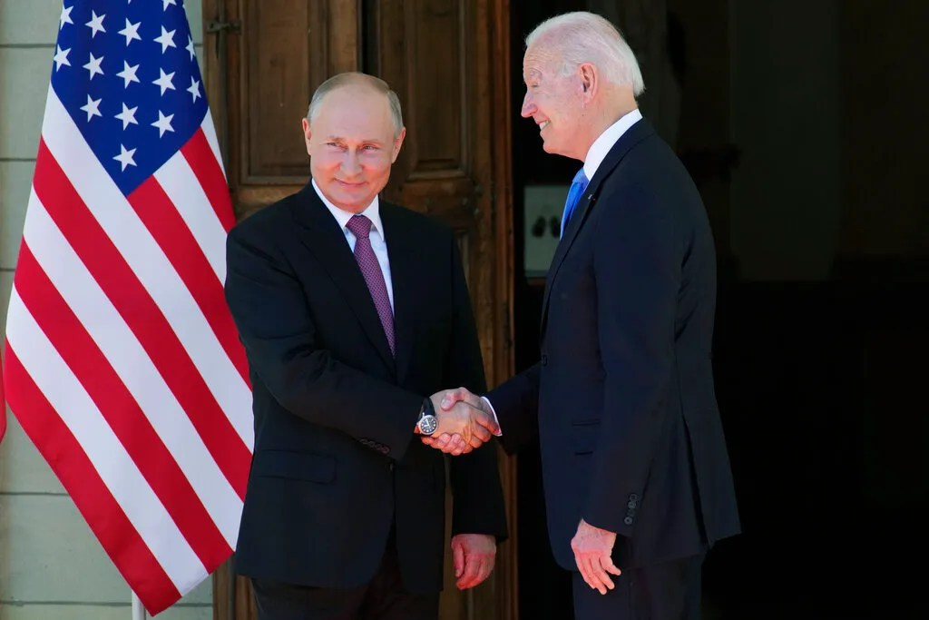 Russian President Vladimir Putin, left, and US President Joe Biden shake hands as they meet at the