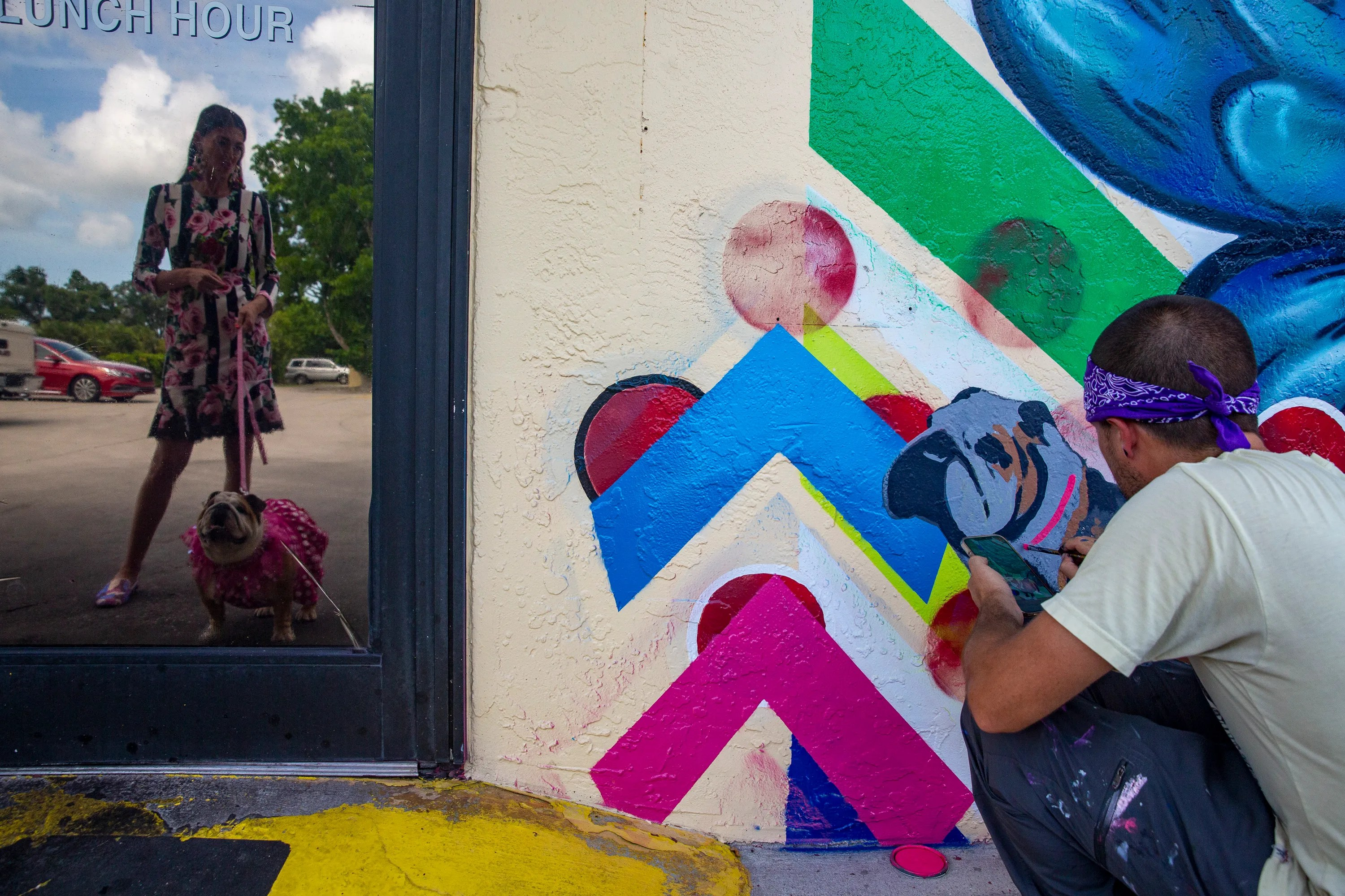 Emily Monty, co-owner of Spanky's Speakeasy watches artist Marus Zotter work on adding English bulldog named Bubbles to her new mural, Friday, July 9, 2021, at Spanky's Speakeasy in Naples.
