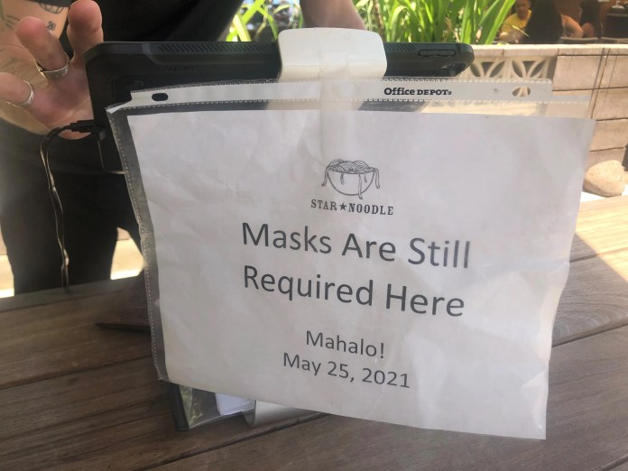 A sign  at the host stand at Star Noodle in Lahaina, Hawaii, reminds guests of Hawaii's indoor mask mandate.