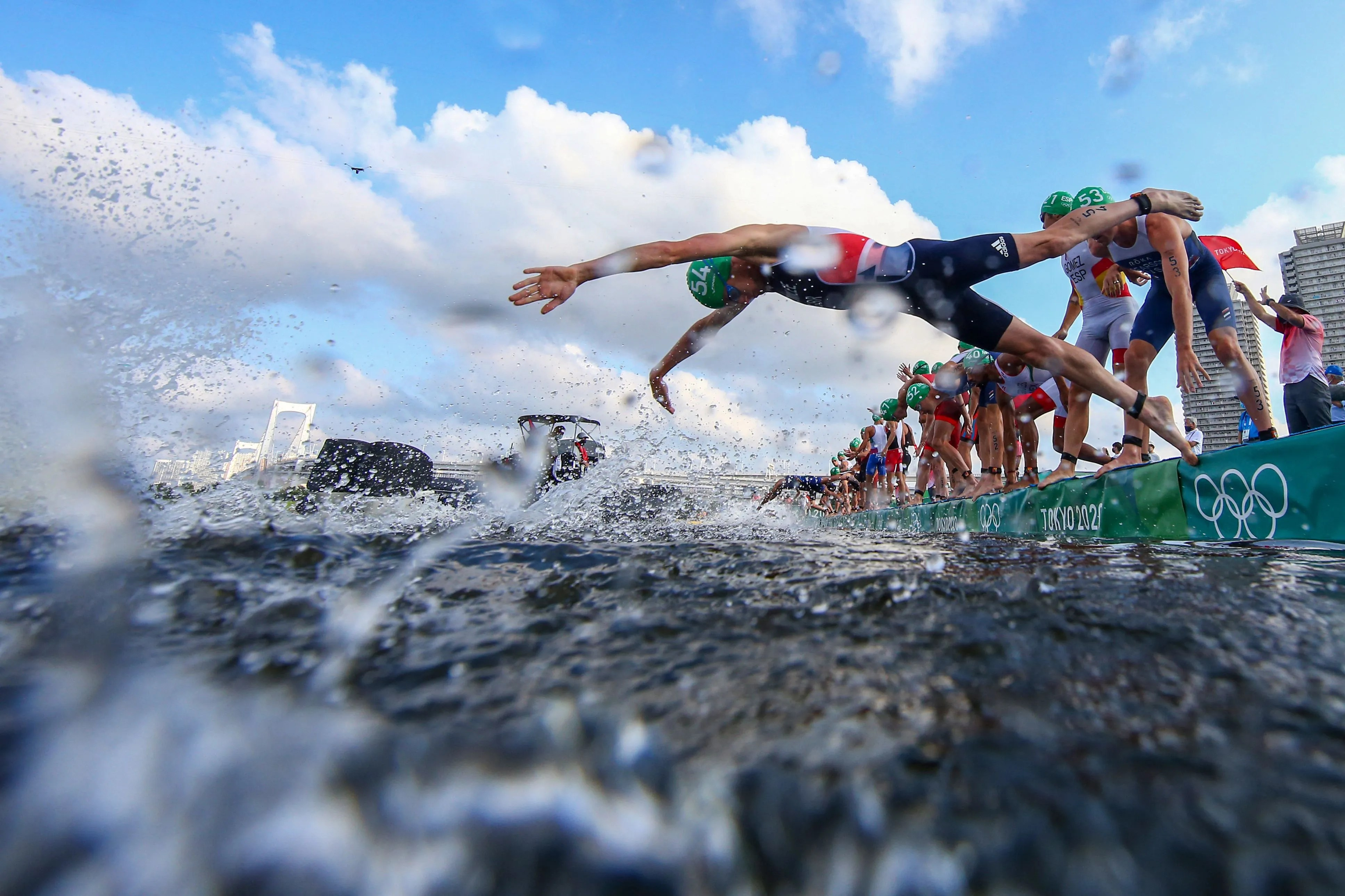 Some athletes dive into the water while others are stranded by a broadcast boat during the men's individual triathlon competition at the Tokyo 2020 Olympic Games.