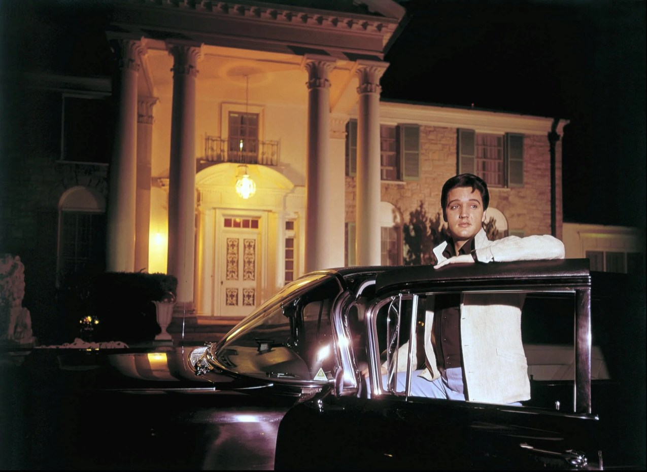 Elvis Presley posed with one of his cars outside Graceland in this photograph published March 7, 1965. Elvis complained of the long sessions with photographers making movie publicity stills: