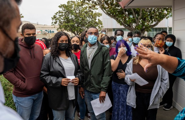 Dozen of students, educators and other community members stand in the front entrance of the Salinas Union High School District office in Salinas, Calif., on Tuesday, Aug. 24, 2021.