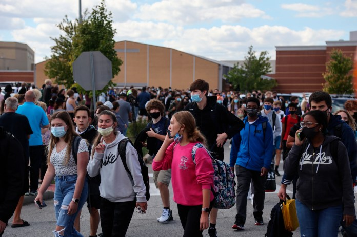 Students wait outside Lake Central High School after a report of an active shooter Wednesday morning, Sept. 8, 2021 in St. John, Ind. No shots were fired, according to school officials.