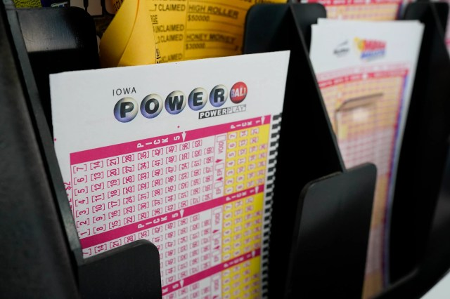 In this Jan. 12, 2021 file photo, blank forms for the Powerball lottery sit in a bin at a local grocery store, in Des Moines, Iowa. The giant Powerball jackpot has grown even bigger, with officials raising the estimated payout ahead of Saturday, Oct. 2, drawing.