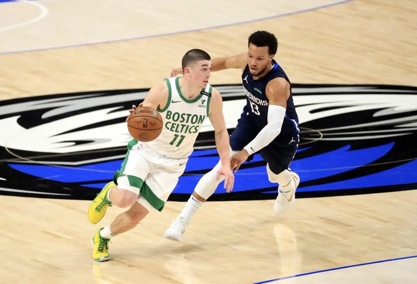 Feb 23, 2021; Dallas, Texas, USA; Boston Celtics guard Payton Pritchard (11) drives to the basket as Dallas Mavericks guard Jalen Brunson (13) defends during the first half at American Airlines Center.