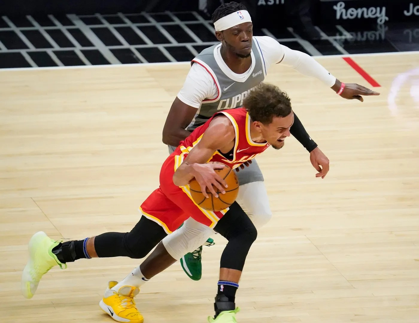 Mar 22, 2021; Los Angeles, California, USA; Atlanta Hawks guard Trae Young (11) dribbles the ball past LA Clippers guard Reggie Jackson (1) during the second quarter at Staples Center.
