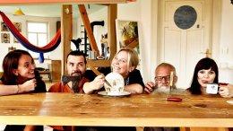 Lustige Menschen an einem Holztisch