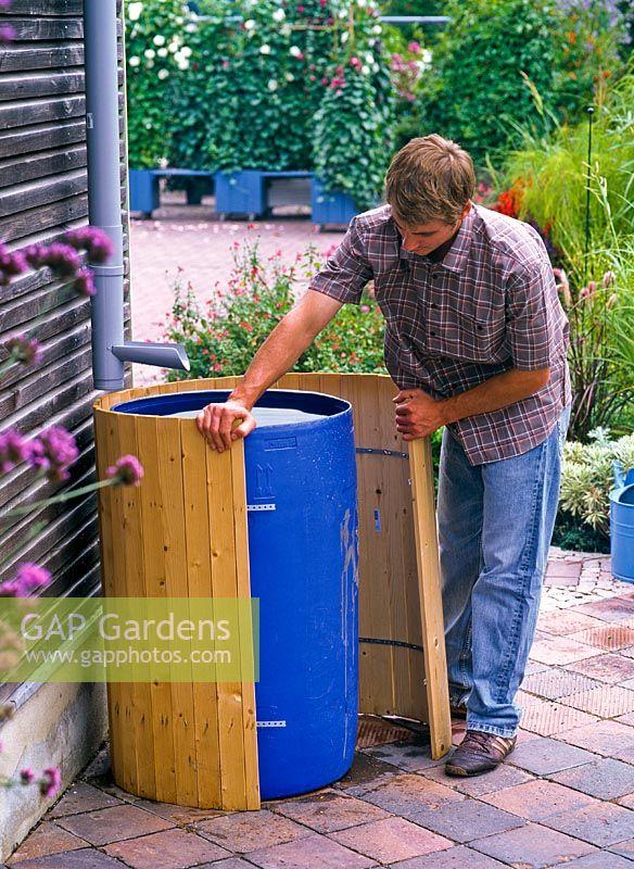 GAP Gardens  Disguising water butt  Man securing wooden slats around blue plastic water butt
