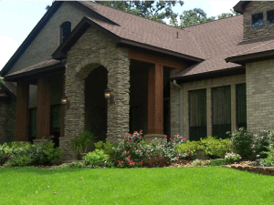 residential landscaping at home with green grass lush plants and stone border