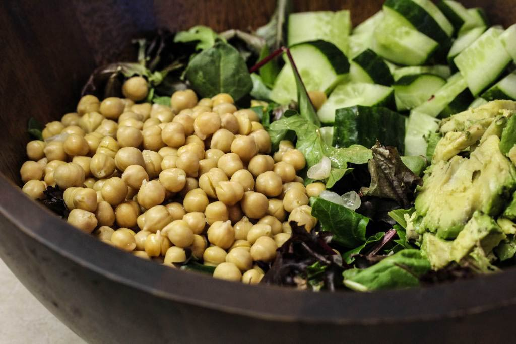 Add ingredients to salad bowl for your avocado and greens salad with lemon mint dressing.