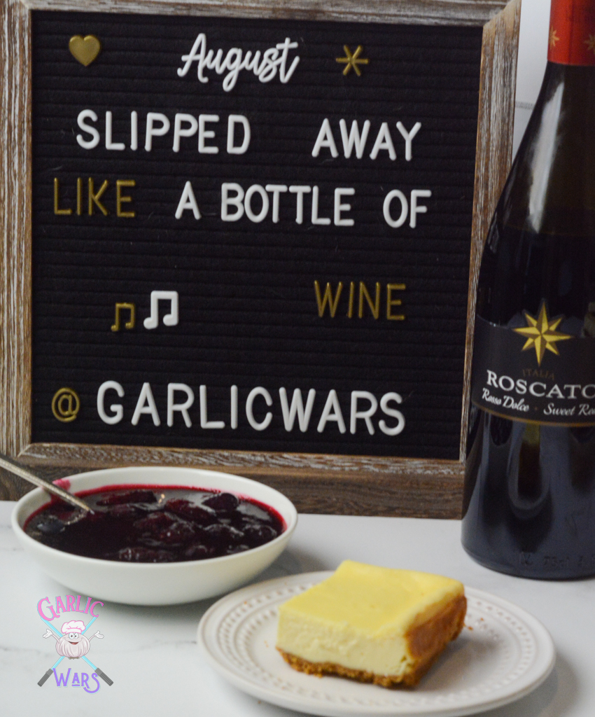 """cheesecake bar on small white plate with red wine berry sauce in small white bowl, in front of letterboard that reads lyrics from a Taylor Swift song """"august slipped away like a bottle of wine"""""""