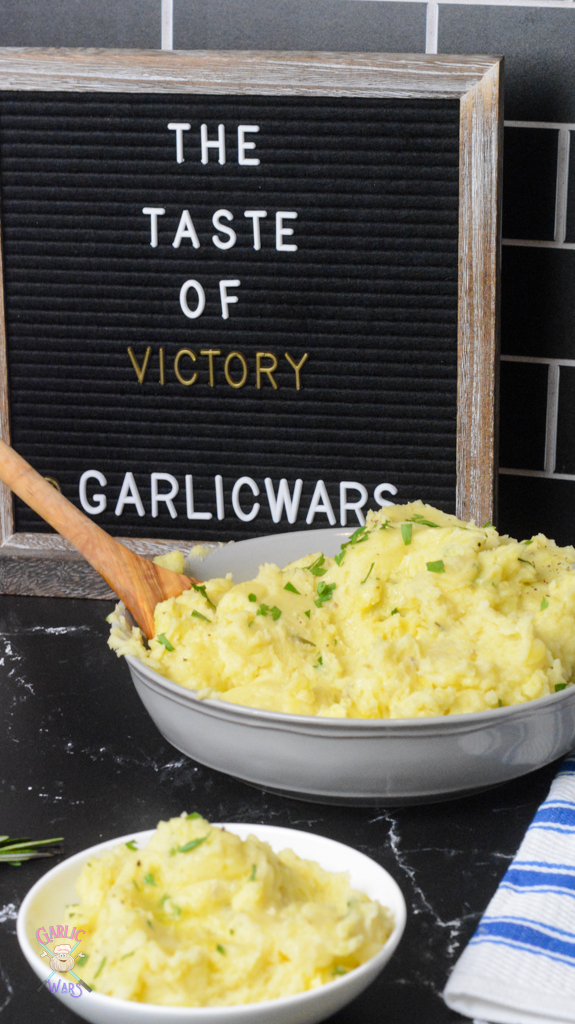 """A large grey bowl of mashed potatoes, with a smaller white bowl of mashed potatoes. A letterboard sign in the background reads """"The taste of victory"""""""