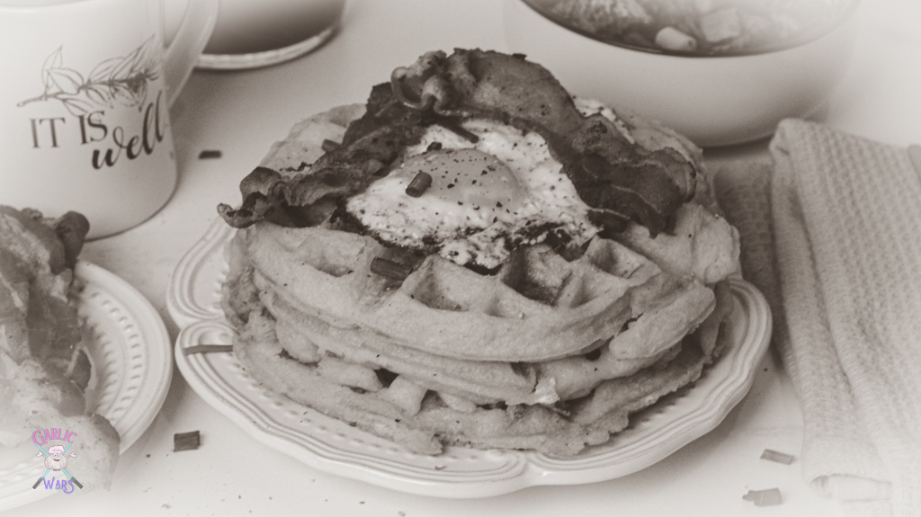 """A plate with waffles, topped with bacon and a fried egg, with a plate of bacon on the side, and a coffee mug that reads """"it is well."""" A black and white picture to represent the style of WandaVision."""