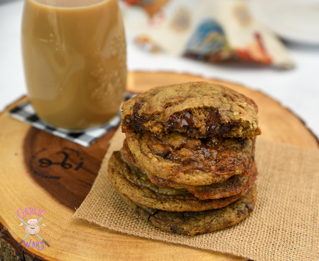stack of coffee chocolate chip cookies with coffee in the background