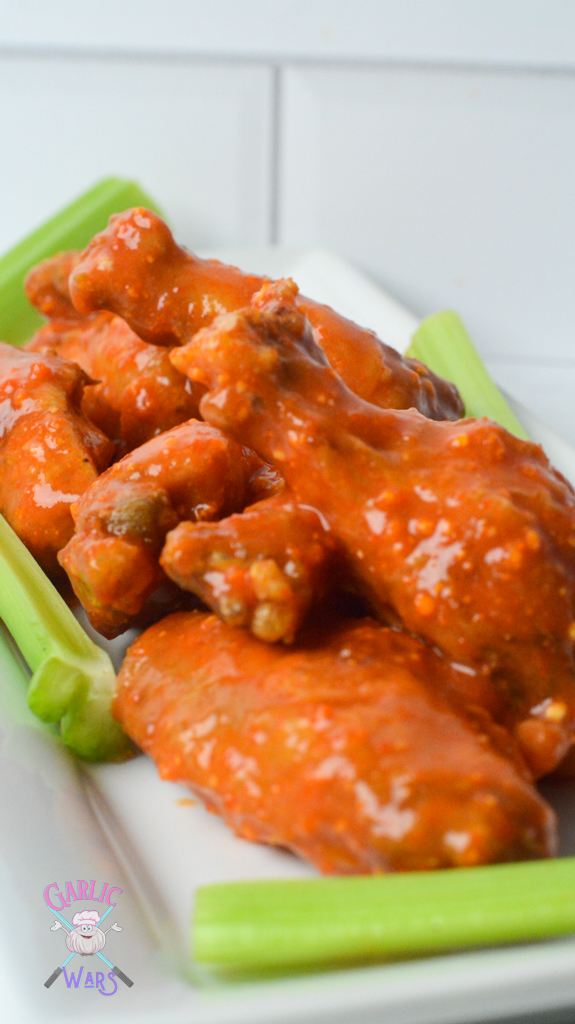 air fryer chicken wings tossed in buffalo sauce on a white plate with celery