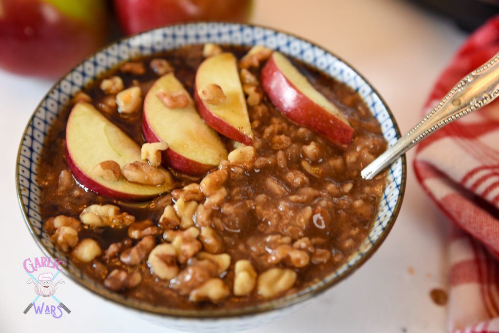 Apple pie oatmeal topped with sliced apples and walnuts.