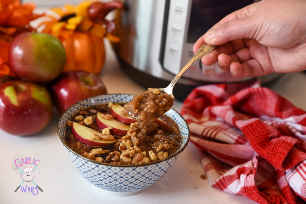apple pie oatmeal topped with sliced apples and walnuts, with apples and a red plaid towel.