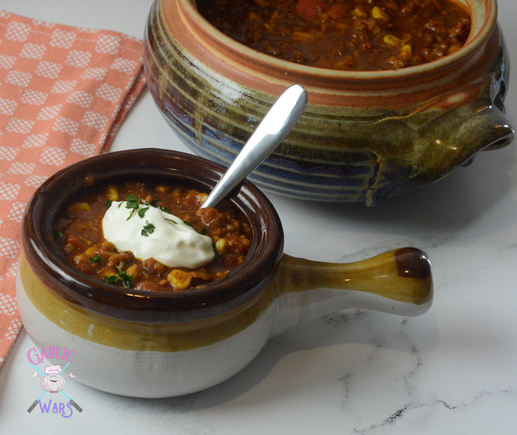 small bowl of pumpkin chili topped with sour cream, in front of large pot of chili