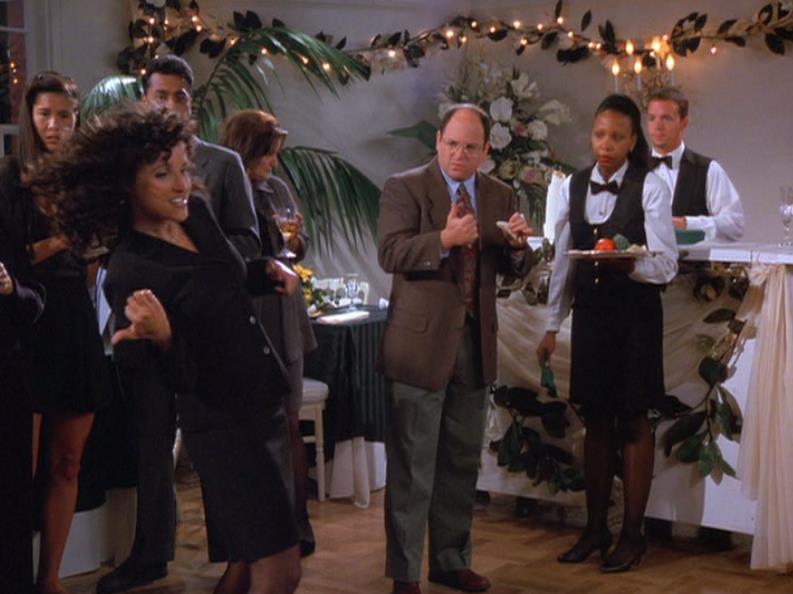 George watches Elaine dance.