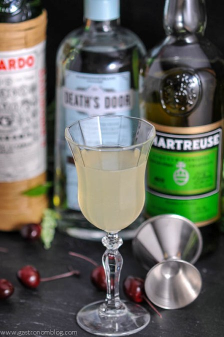 The Last Word Cocktail in a tall coupe glass with a jigger and bottles of gin, green chartreuse and maraschino liqueur.