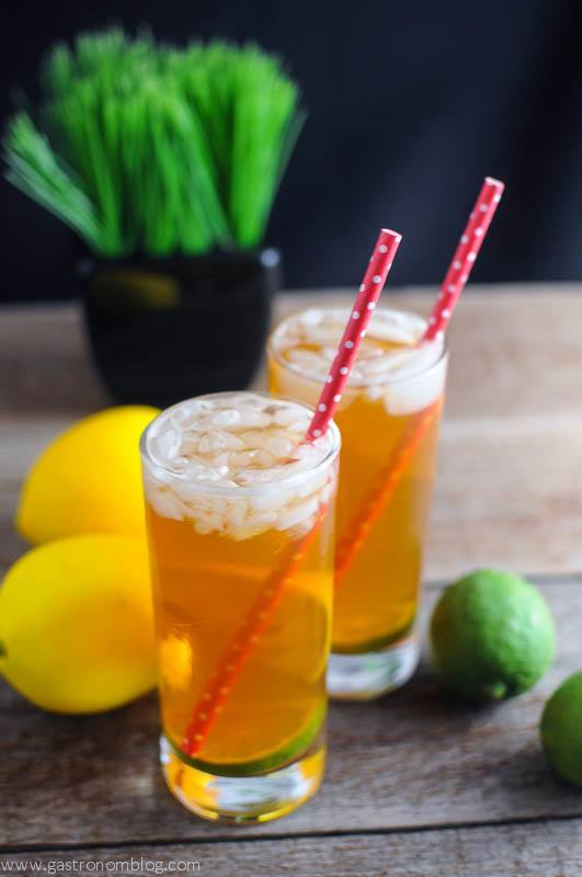 Pimm's Cup Cocktail in two highball glasses with red dot straws. Lemons, limes and grass in background