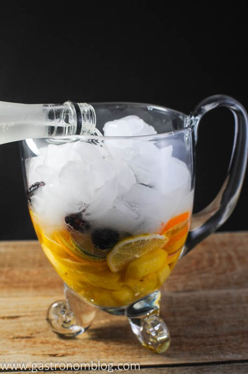 Clear pitcher with limes, pineapple, lemons, oranges, blackberries topped with ice. Pouring in the wine.
