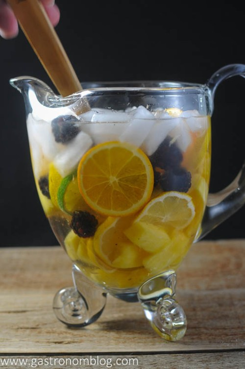 Wood spoon stirring in a clear pitcher filled with ice, white wine, blackberries, pineapple, lemons and oranges