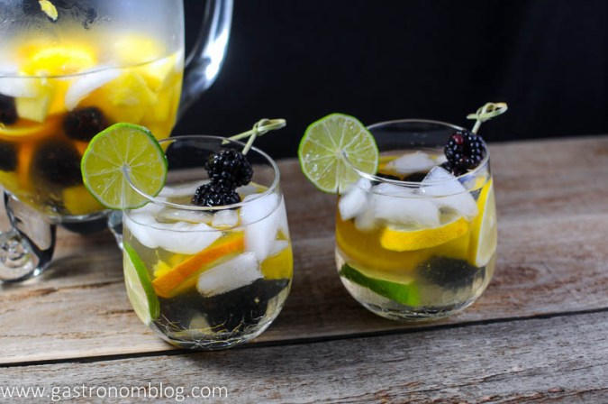Two wine glasses filled with white sangria with limes, blackberries, oranges, lemons and pineapples. Pitcher in background