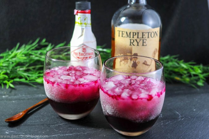 Red Beet Shrub Cocktail in two wineglasses, wooden spoon, cherry bitters bottle and whiskey bottle in background