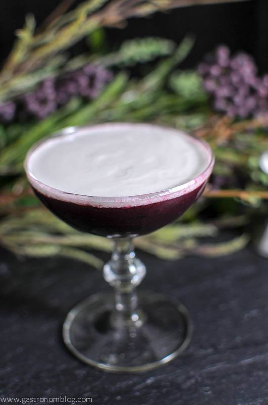 The Black Scot cocktail in a cocktail coupe, flowers in background