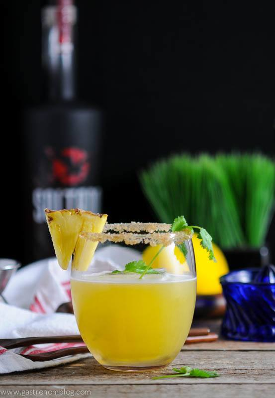 Pina de Fuego cocktail with cilantro and pineapple. Napkin, grass, juicer and tequila bottle in background