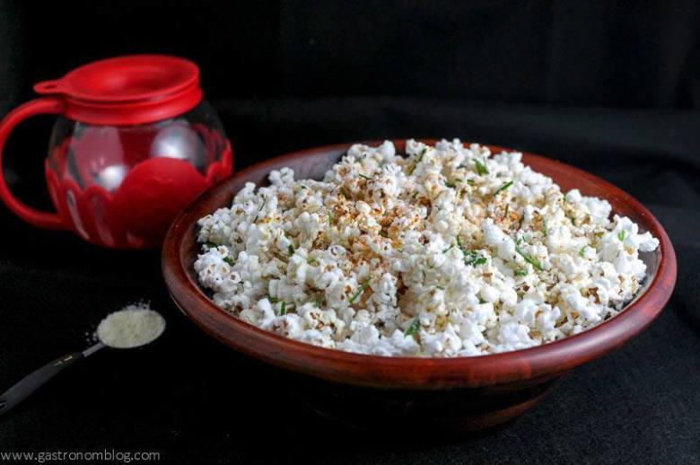 Popcorn in a wooden bowl with popcorn popper in background