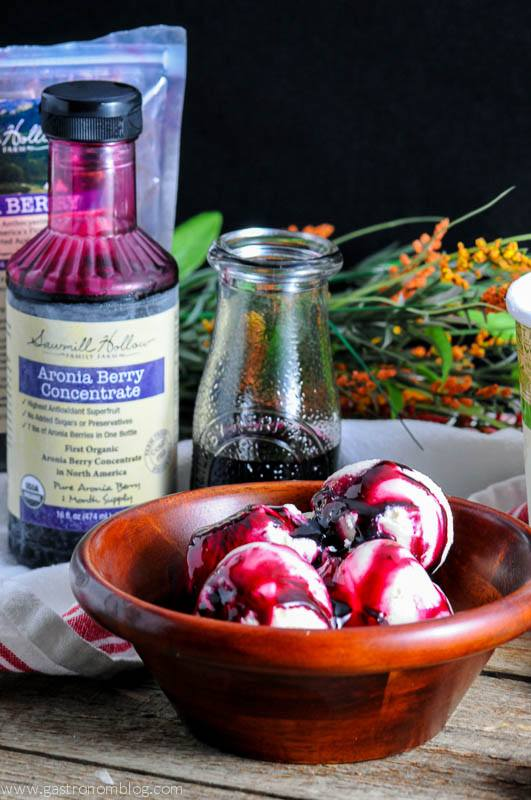 Aronia Berry Syrup on ice cream in a wooden bowl. Aronia berry bottle and bag in back with flowers