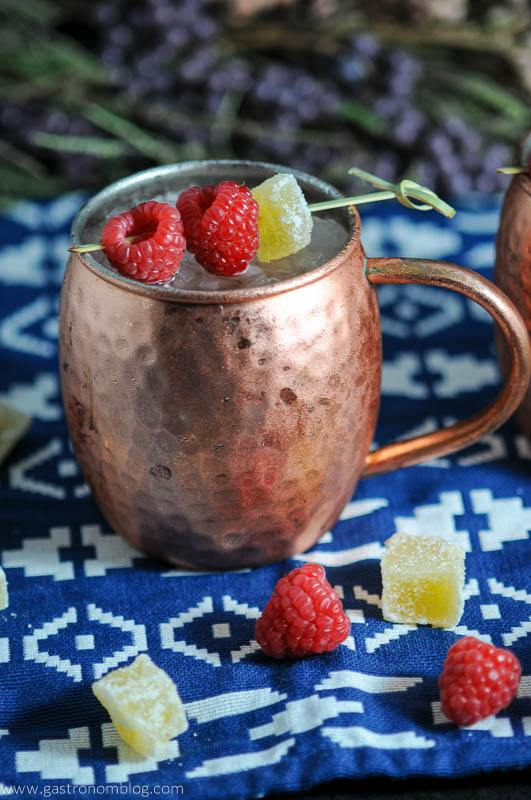 Hatch Chille and Raspberry Moscow Mule in copper mug with crystallized ginger and raspberries on blue and white napkin