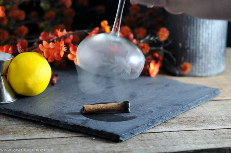 The Clove and Cider Cocktail glass being smoked with burning cinnamon. Flowers, lemon, and jigger in background