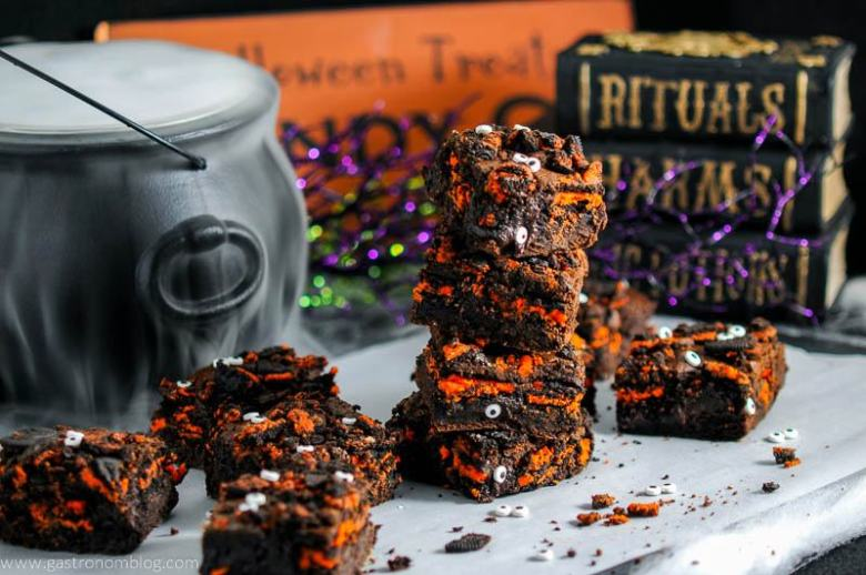 Halloween Oreo Monster Brownies on parchment paper with eyeballs, dry ice in cauldron behind with books and halloween signs