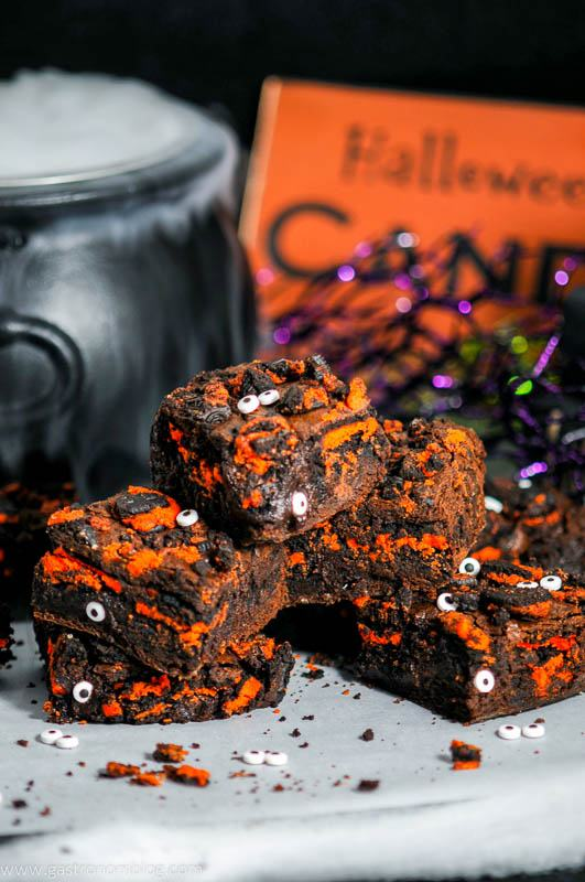 Halloween Oreo Monster Brownies with eyes on parchment paper. Cauldron with dry ice and Halloween sign behind
