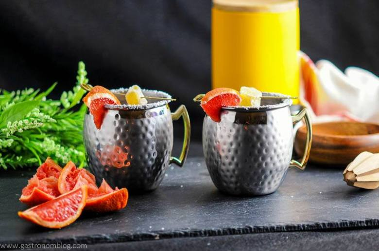 Grapefruit Smoked Salt London Mule in copper mugs, grapefruit wedges with ginger and salt rims. Reamer, flowers, wooden bowl and yellow canister