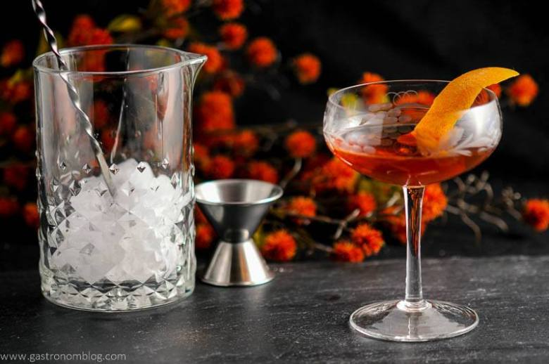 The Woodsman - An Apple Brandy and Ginger Cocktail in a coupe, mixing glass and bar spoon, jigger and flowers in background