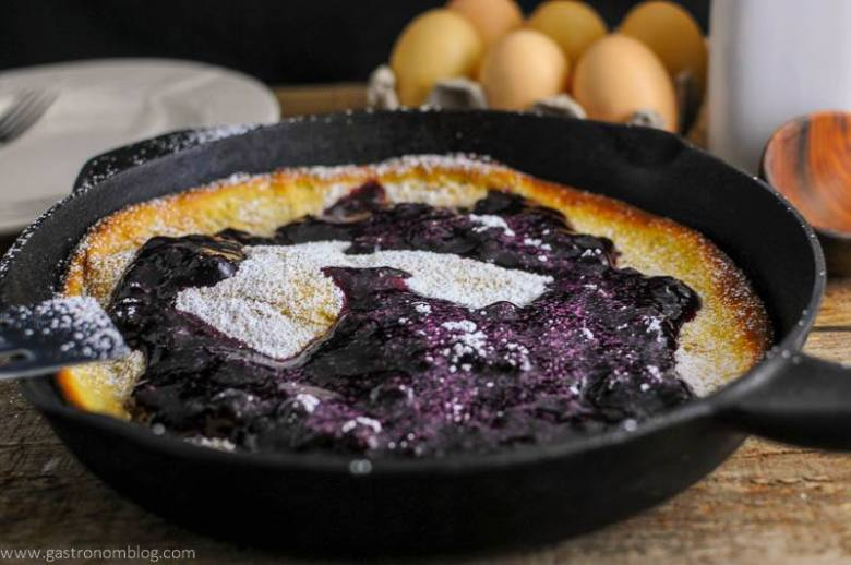 Dutch Baby Pancake with Blueberry Whiskey Sauce in skillet. Eggs in background