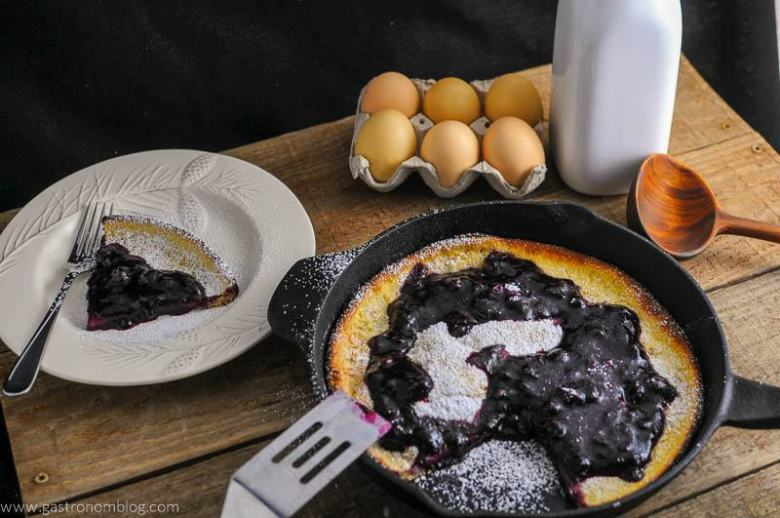 Dutch Baby Pancake with Blueberry Whiskey Sauce in a skillet, some on white plate, eggs, milk bottle and wooden spoon in background