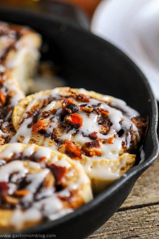 Bourbon bacon cinnamon rolls in a cast iron pan.