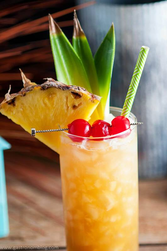 Close up shot of the Fall in Paradise Cocktail, garnished with candied cherries, pineapple and pineapple leaves, a tropical straw and crushed ice