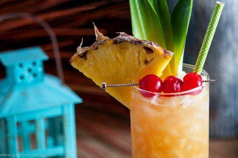 The Fall in Paradise Cocktail garnished with cherries, pineapple wedge and pineapple leaves.